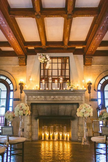 a fireplace styled with candles inside and on the mantel and neutral floral arrangements in bottles and vases