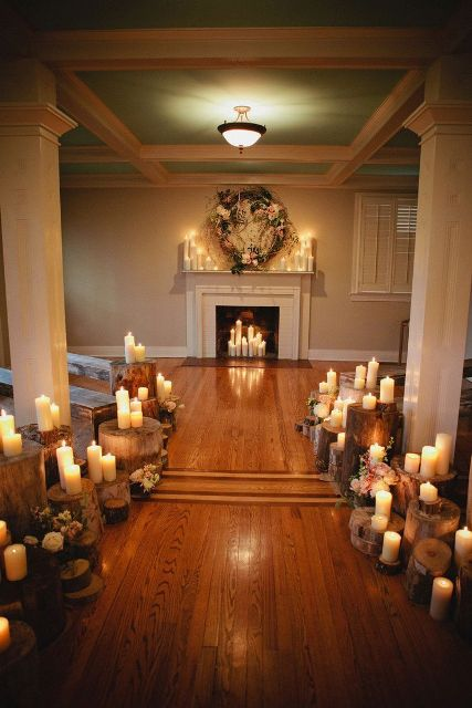 a faux fireplace with candles inside and on the mantel and a lush floral and greenery wreath over the mantel for a wedding ceremony
