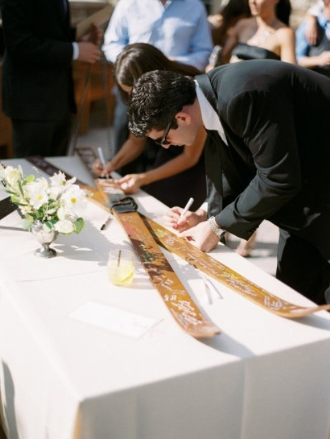 guests leaving wishes and their names on large skis   this is a great idea for a ski resort wedding
