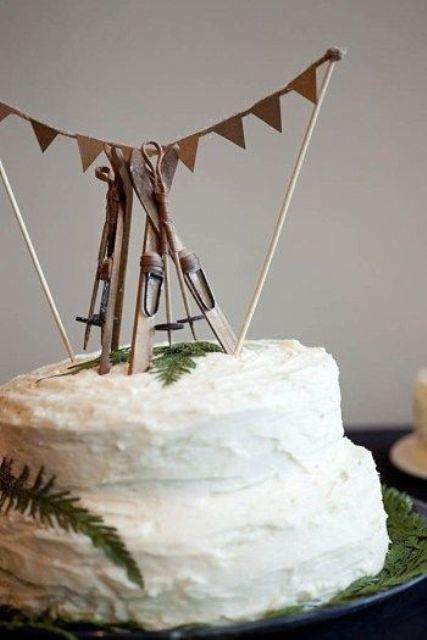 a textural buttercream wedding cake topped with greenery, skis and other ski stuff is a very beautiful and cozy dessert for a ski resort wedding