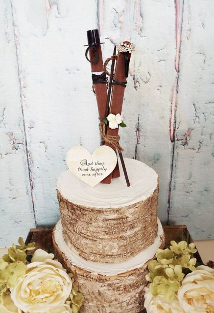 a bark wedding cake topped with a heart and with skis in a veil and a top hat is a whimsy and fun wedding cake for your ski resort wedding