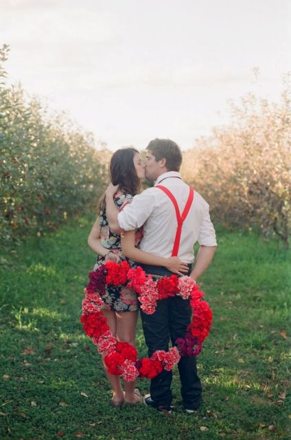 a bright floral heart shaped wreath and red suspenders to accent this Valentine engagement photo