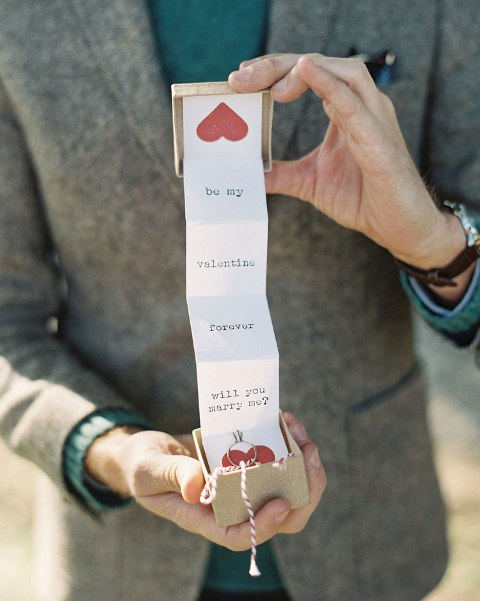 a groom popping up the question in a creative way - with a box with letters and hearts is a lovely vintage-inspired idea