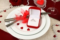 a pretty burgundy, red and white Valentine engagement table with a white runner and plates, with little red hearts, pearls and an engagement ring