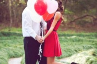 a pretty engagement pic on Valentine's Day with a bunch of blush and red balloons, a bride-to-be wearing a short red dress with black shoes