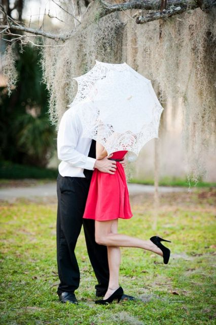 a red mini dress and a lace umbrella for pretty Valentine engagement pics with much romance and elegance