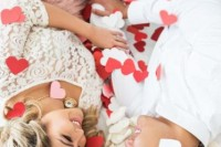 a pretty and easy Valentine's Day engagement pic with lots of paper hearts is a perfect idea of a photo that is easy to realize