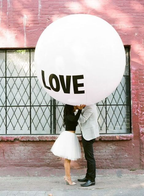 a romantic Valentine's Day engagement pic with an oversized white balloon and a couple wearing a monochromatic outfit