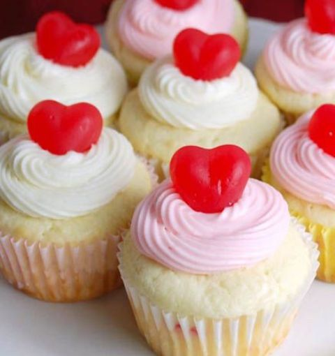 cupcakes with pink and white frosting and heart toppers are lovely Valentine wedding desserts or appetizers