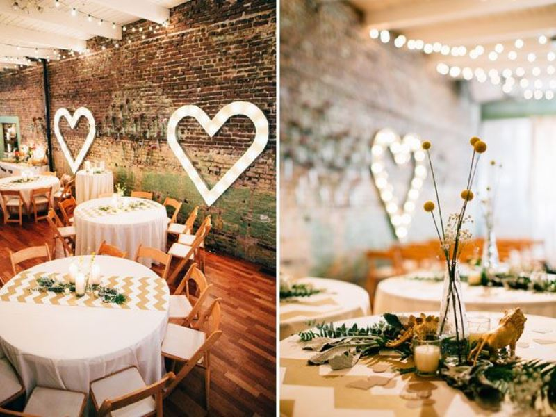 a stylish industrial wedding venue with brick walls, marquee hearts and lovely chevron runners and billy balls