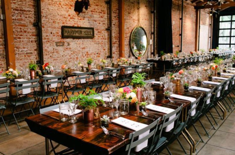 an industrial wedding venue with red brick walls, pipes, bright blooms and greenery and potted succulents for a bold look