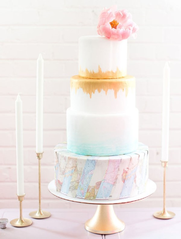 a chic wedding cake with an ombre effect, an aqua and a gold touch and a tier featurign colorful world maps