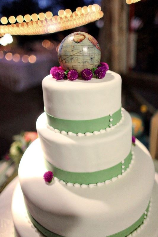 a white wedding cake with a green ribbon and a globe topper plus some blooms for a bright touch