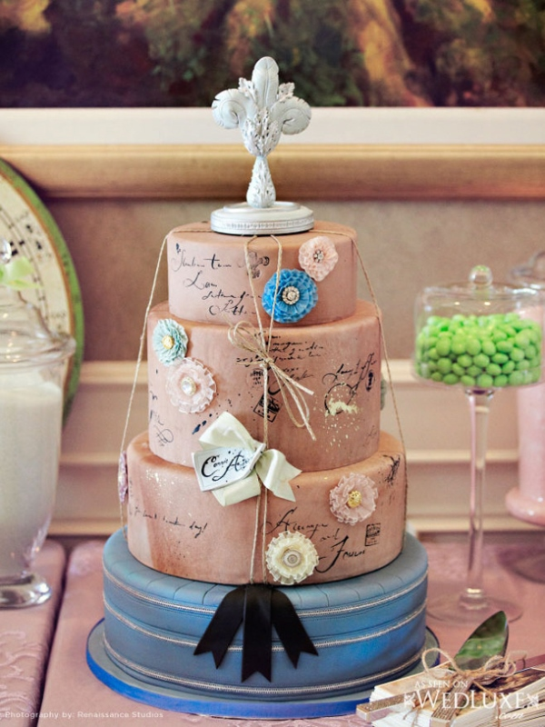 a taupe and blue wedding cake imitating postcards and letters and some twine and bows