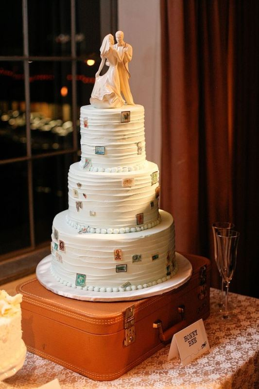 a textural white wedding cake decorated with edible stamps hints on travelling