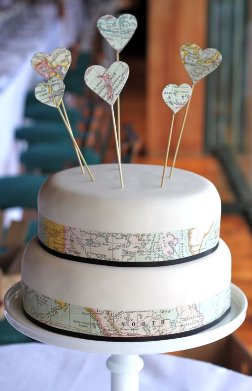 a white wedding cake with world maps and heart toppers made of a world map