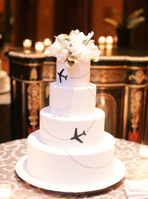 a white wedding cake decorated with black airplanes and fresh white blooms on top for a chic look