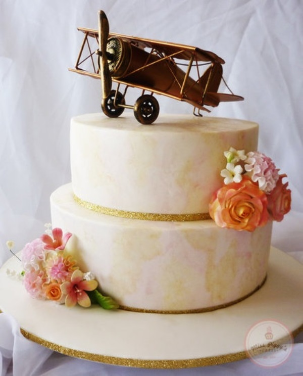 a pastel abstract wedding cake with sugar blooms and a cool airplane topper