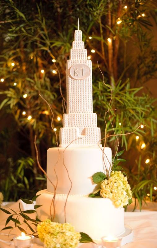 a chic white wedding cake topped with an Empire State Building and fresh blooms