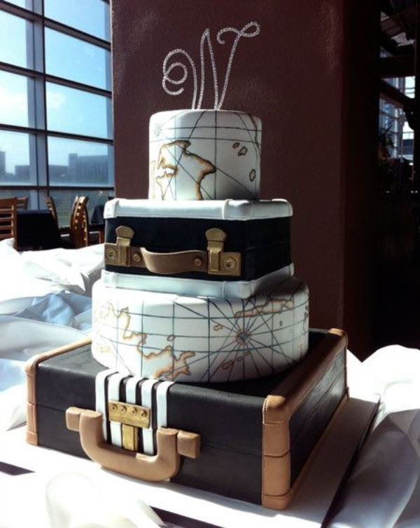 a gorgeous wedding cake featuring suitcase and map tiers and a glam embellished monogram topper