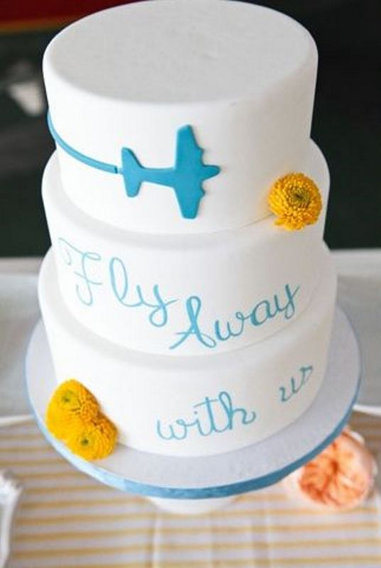a white wedding cake with a plane and a wish plus some bright yellow blooms