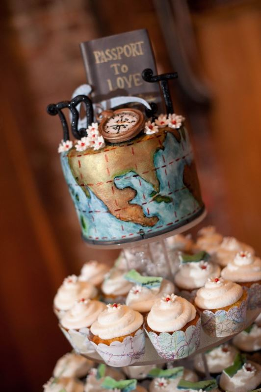 a bold world map wedding cake topped with monograms, sugar blooms and a book is a whimsy idea