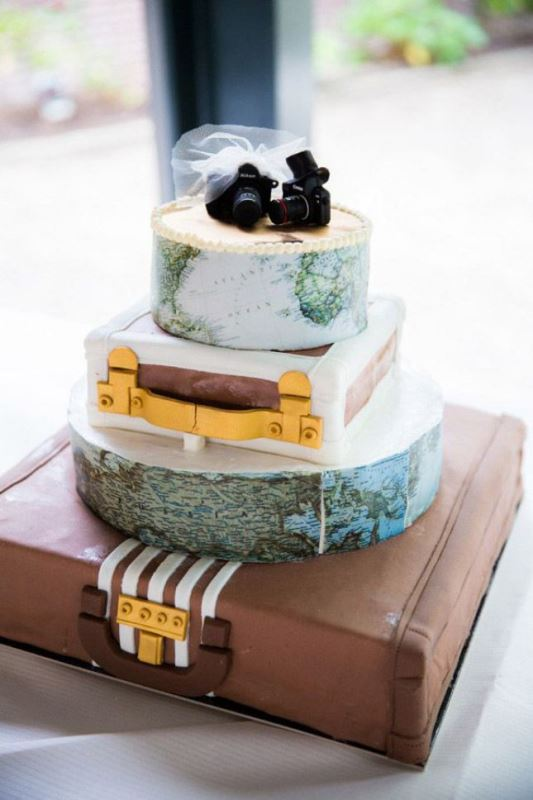a whimsical wedding cak featuring map and suitcase tiers plus little cameras on top for a touch of fun