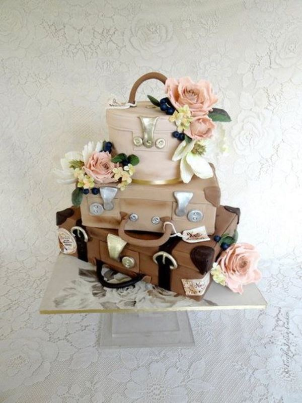 a unique wedding cake featuring layers looking like vintage suitcases or boxes and sugar blooms screams travelling