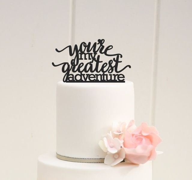 a chic white wedding cake with sugar blooms and a black calligraphy topper telling of adventures and travelling