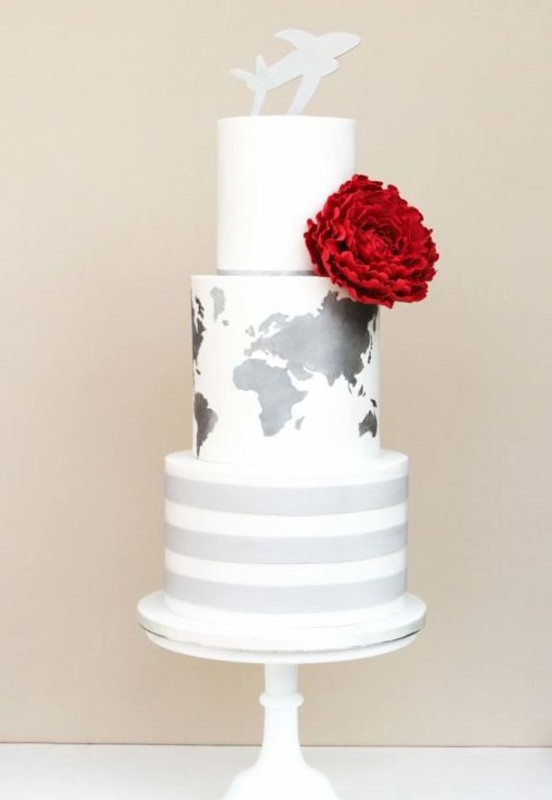 a white wedding cake with a striped and a map tier plus a bright red flower and a fun topper