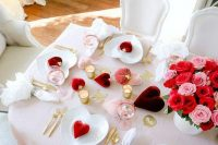 a beautiful Valentine engagement tablescape with blush linens, red and burgundy hearts and bold blooms