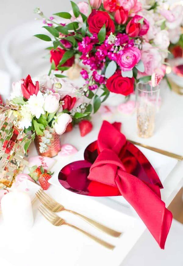 a beautiful Valentine engagement tablescape with pink heart chargers, gold cutlery, bold blooms and greenery