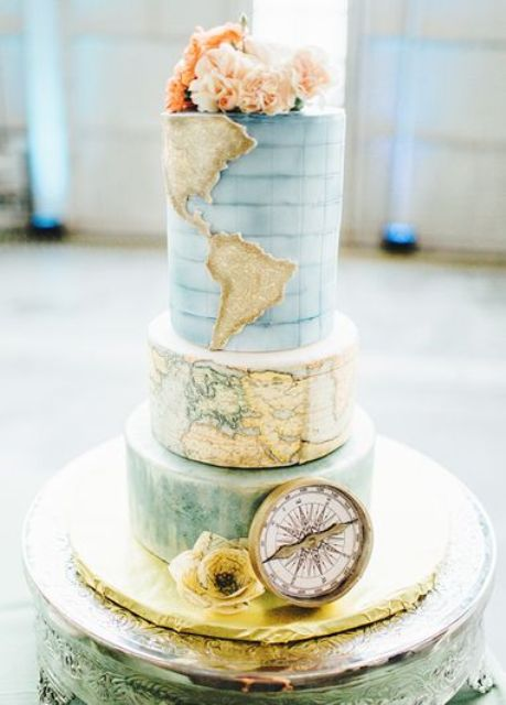 a beautiful travel-themed wedding cake with map and ombre layers, fresh blooms and a compass for decor