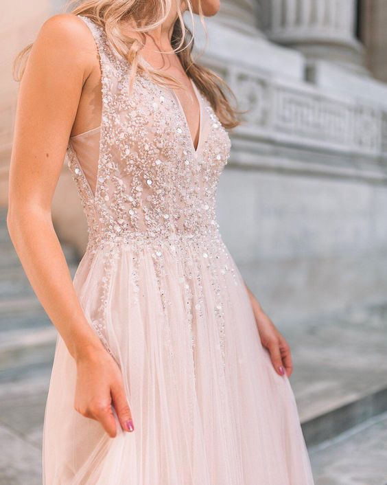 a blush wedding dress with embellishments, a deep neckline and cutout sides is a chic and romantic option to try