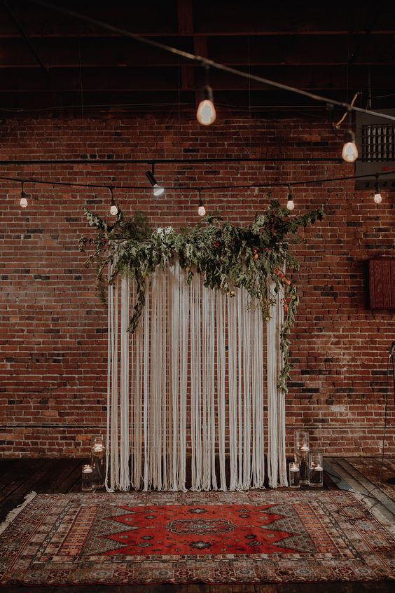 a boho industrial wedding ceremony space with a fringe backdrop, greenery on top, floating candles and a boho rug