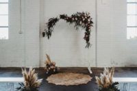 a boho industrial wedding ceremony space with a white arch decorated with greenery and pink blooms, greenery and pampas grass