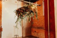 a boho industrial wedding space with lush blooms, greenery, boho rugs and candles