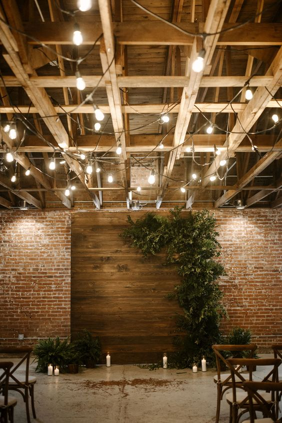 a boho wedding ceremony space with a wooden backdrop with lush textural greenery, pillar candles and chairs