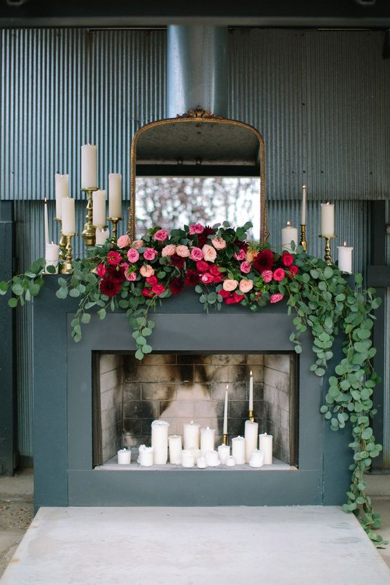 a bold modern fireplace with lots of candles inside and on the mantel, with an antique mirror and a lush floral and greenery garland