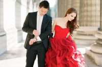 a bride-to-be wearing a strapless red dress with a layered skirt is a lovely and bold idea for a more formal engagement