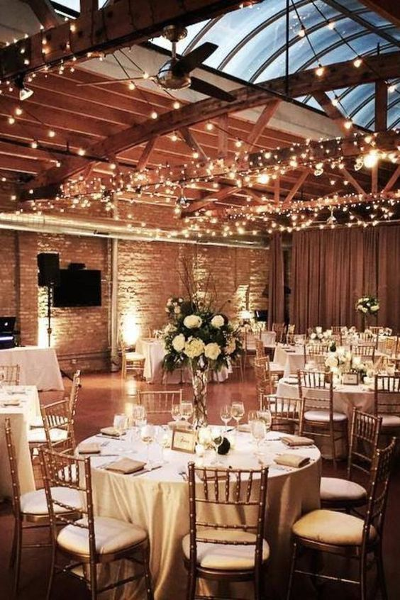 a bright lit up wedding venue with brick walls, wooden beams and lights and lush white florals