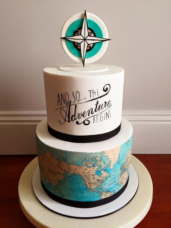 a bright wedding cake with a white calligrpahy and a map tier plus a compass topper