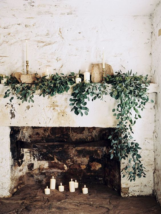 a chic fireplace with candles inside and on the mantel, with cascading greenery and stones