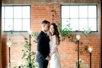 a chic industrial wedding ceremony space decorated with greenery, white blooms and catchy floor lamps