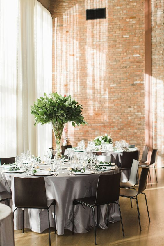 a chic industrial wedding venue with red brick walls, neutral curtains, grey tables and black chairs and greenery centerpieces