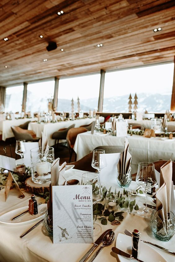 a chic rustic ski resort reception space with greenery, candles, pinecones and neutral linens and chic menus