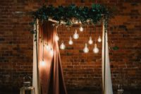 a chic wedding arch decorated with greenery, bulbs, elegant curtains, candles and potted cacti