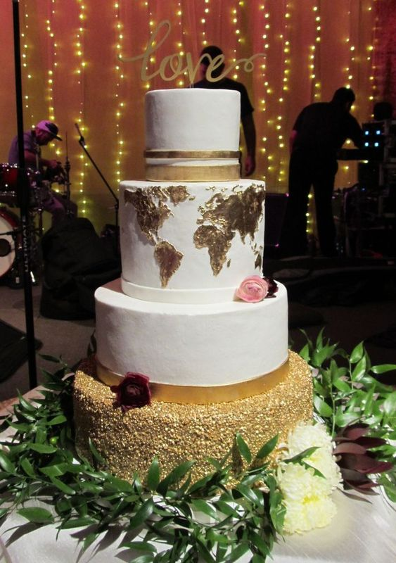 a chic wedding cake with a gold glitter tier, two white ones and a gold world map tier plus a calligraphy topper
