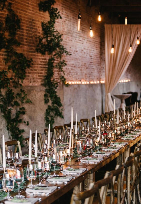 a cool industrial reception space with brick and cocnrete walls, greenery, lights and candles on the table