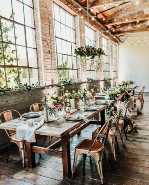 a cool industrial wedding venue with brick walls, hanging lights, wooden tables and copper chairs plus bright flowers